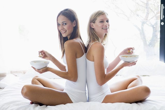 Two women sitting on bed eating