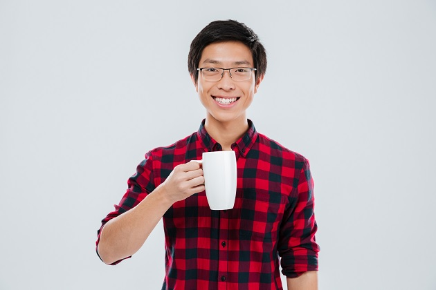 young man holding cup of tea