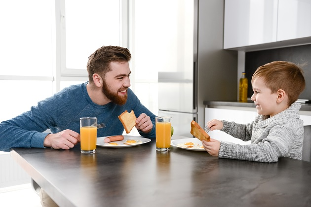 father eating at kitchen with his son