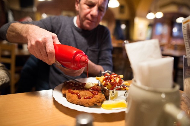 man in restaurant use ketchup