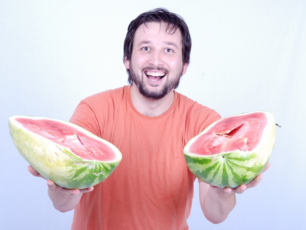 young man offers watermelons